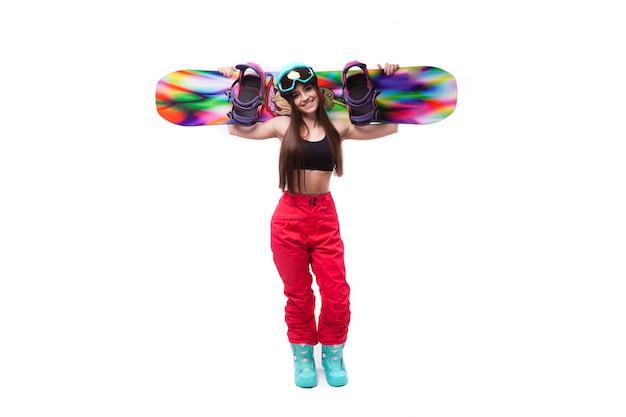 黒の短いタンクトップの若い美しさの女性はスノーボードを保持します。