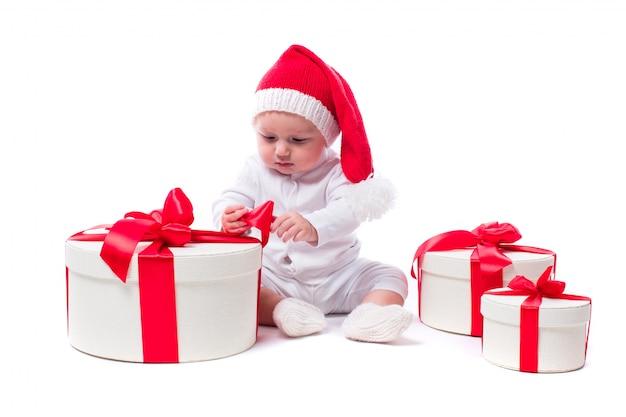 新年の帽子と白い体に座っている美しい子供