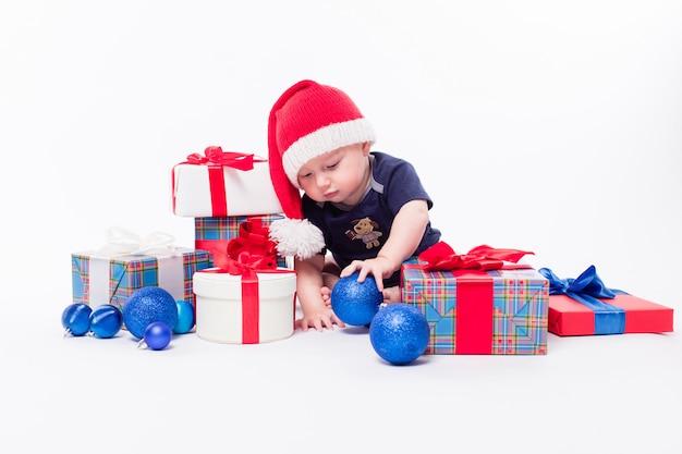 クリスマスのおもちゃの中でかわいい幼児が新年の帽子に座っています。