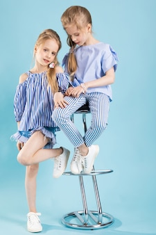 水色の服を着た双子の女の子がバースツールの近くでポーズをとっています。