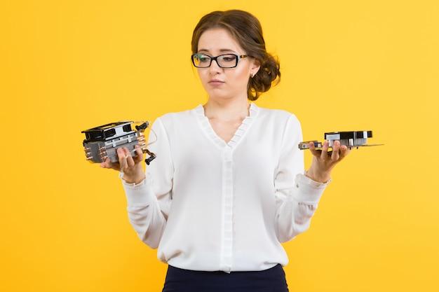Портрет уверенно красивой озадаченной смущенной молодой женщины с деталями компьютера оборудования