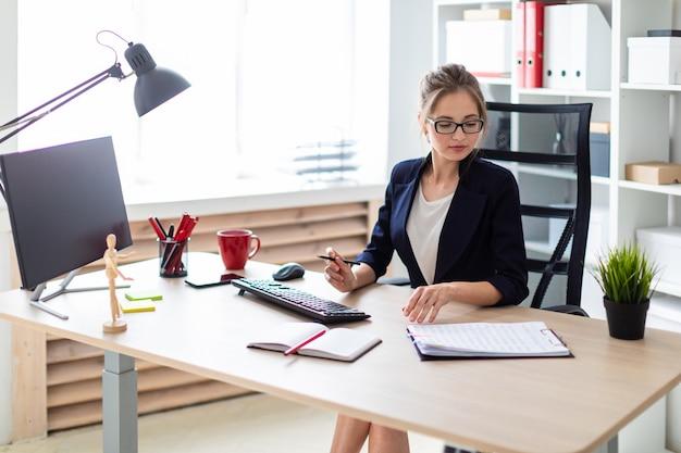 若い女の子がコンピューターの机に座って、手に鉛筆を持ち、ドキュメントを操作しています。