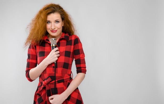赤い格子縞のシャツの若い赤い髪の少女。若い女の子がマイクで立っています。