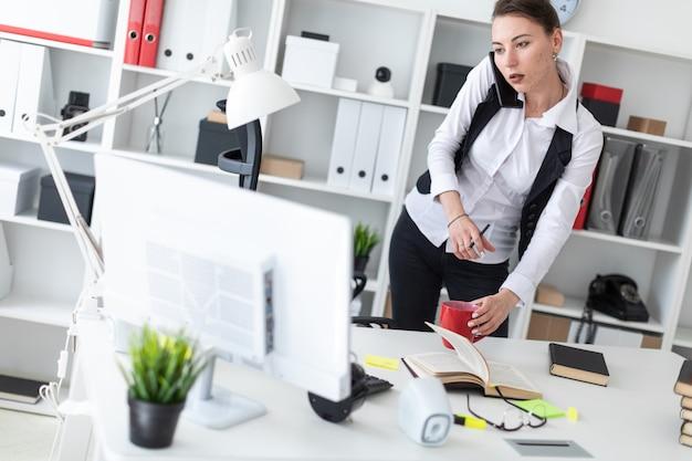 若い女の子がコンピューターの机の近くに立って、手に鉛筆と赤カップを持っています。少女の前に開かれた本があります。