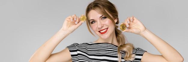 コインを持って幸せな少女。ストライプのブラウスとオレンジ色のズボンの女の子。