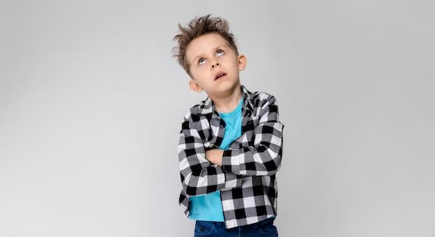 格子縞のシャツ、青いシャツ、ジーンズのハンサムな男の子が立っています。少年は腕を胸にかざした。少年は目を閉じた