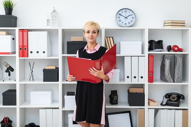 若い女の子がオフィスに立ち、赤いフォルダーを手にしています。