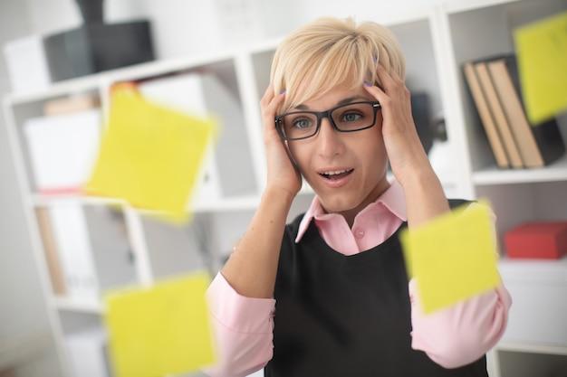 若い女の子は、ステッカーが貼られた透明なボードの近くのオフィスに立ち、手を頭に抱えています。