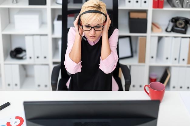 コンピューターのテーブルに座って、彼の頭に手を繋いでいるヘッドフォンを持つ少女。