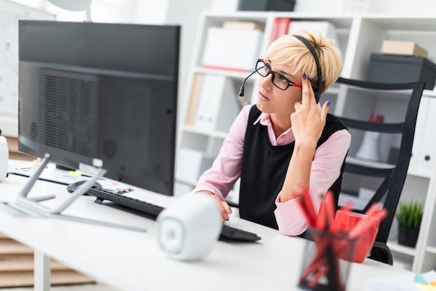 コンピューターのテーブルに座っているヘッドフォンを持つ少女。