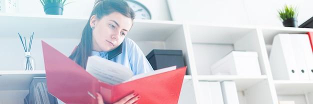 Молодая девушка в кабинете стоит возле укрытия, разговаривает по телефону и просматривает папку с документами.