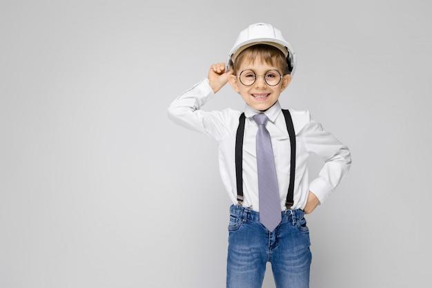 Очаровательный мальчик в белой рубашке, подтяжках, галстуке и светлых джинсах