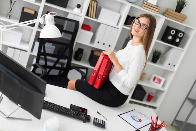 若い女の子はオフィスのテーブルに座って、ドキュメントのフォルダーを保持しています。