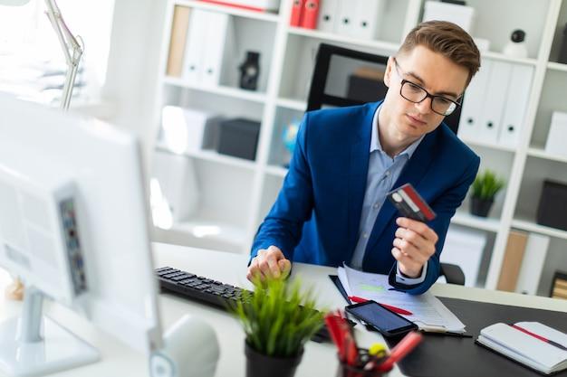 若い男がオフィスのテーブルに座って、銀行カードを手に持って、コンピューターに入力しています。