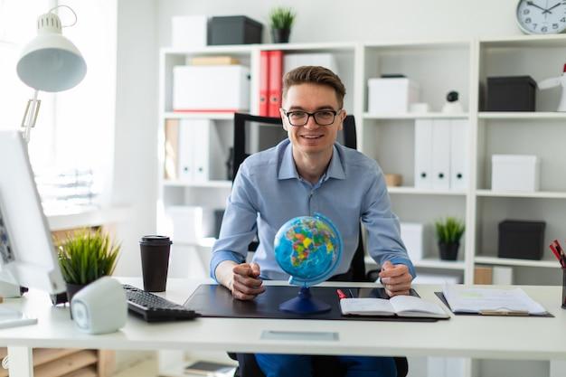 若い男がオフィスのコンピューターデスクに座っており、彼の前には地球が立っています。