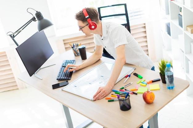 コンピューターの机の近くに眼鏡とヘッドフォンを持つ若い男が立っています。