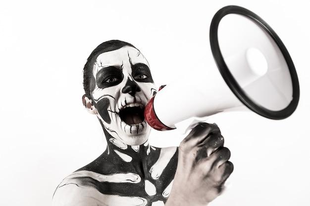 Привлекательная девушка со скелетом держит мегафон