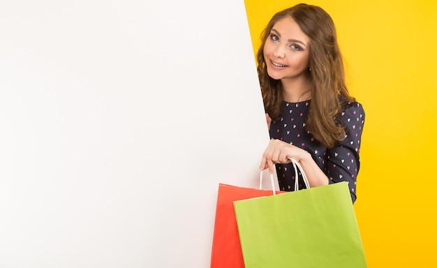 白い空白のプラカードと買い物袋を持つ魅力的な女性