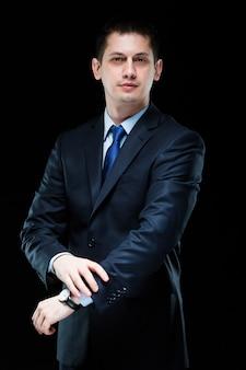 彼のスーツに手で自信を持ってハンサムなスタイリッシュなビジネスマンの肖像画