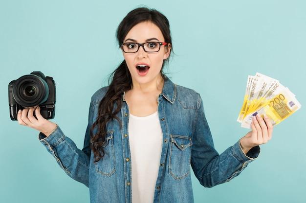 カメラと現金を持つ若い驚く女性