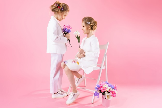 椅子に近いポーズの花の花束と光の服で双子の女の子