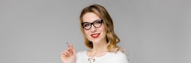 オフィスで立っているクリップボードを保持笑みを浮かべて黒と白の服の魅力的な若い金髪ビジネス女性