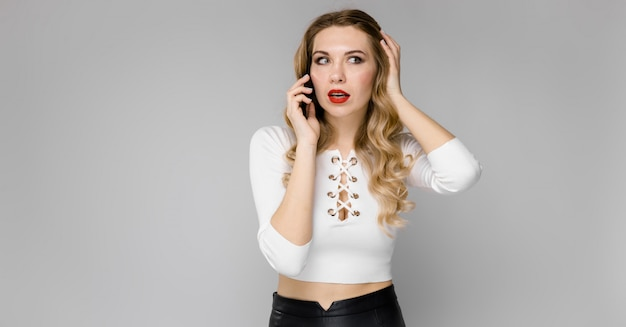 魅力的な若い金髪興奮してオフィスで立っている電話で話して笑っている黒と白の服のビジネス女性