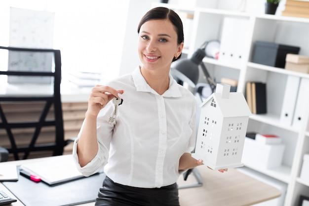 オフィスに立って、鍵と家のレイアウトを保持している若い女の子。