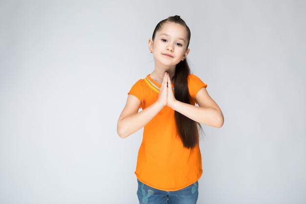 Девушка в оранжевой футболке и синих джинсах