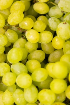 明るい緑のブドウの束、エキゾチックなフルーツ、ベリーの背景のクローズアップ。