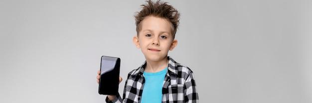 格子縞のシャツ、青いシャツ、ジーンズのハンサムな男の子が立っています。少年は電話を持っています