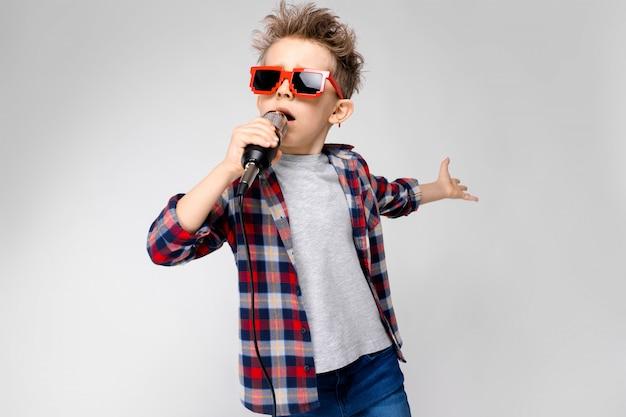 Стоит красивый мальчик в клетчатой рубашке, серой рубашке и джинсах. мальчик в темных очках. рыжий мальчик поет в микрофон