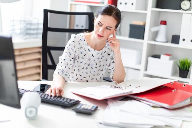 コンピューターデスクのオフィスに座って、ドキュメントを操作し、彼の頭に手を繋いでいる少女。