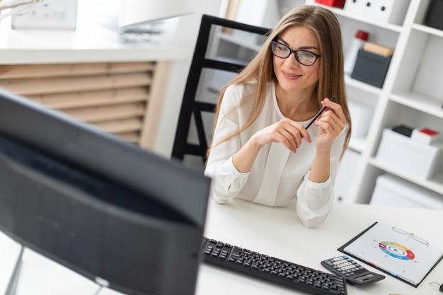 若い女の子がオフィスの机に座って、手に鉛筆を持ってモニターを見ています。