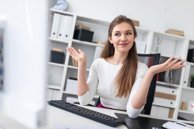 Молодая девушка сидит за компьютерным столом и развела руками в сторону.