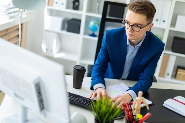 若い男がオフィスのテーブルに座って、ドキュメントとコンピューターを操作します。