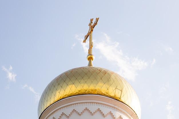 Вид снизу на солнечный солнечный купол христианской церкви с крестом на вершине