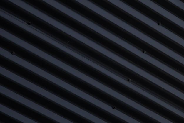 金属の光沢のある黒い波形表面のクローズアップ
