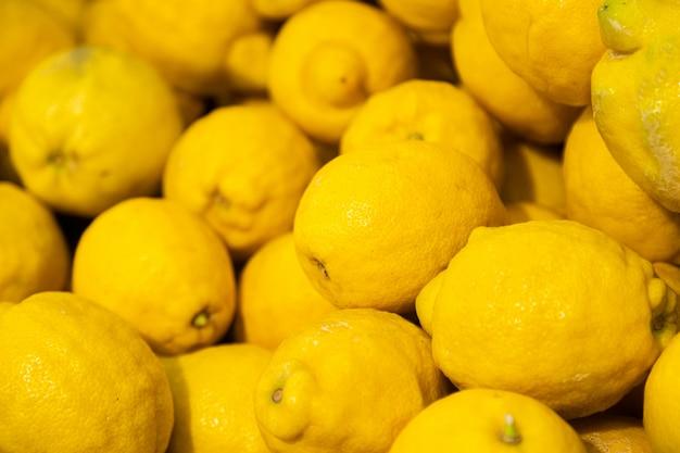 背景の販売のための夏の市場で熟した黄色いレモンの山
