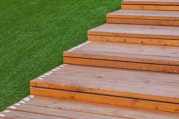 外の緑の芝生の近くの明るい色の木製の階段