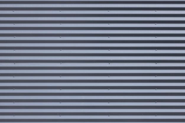日光の下で灰色の金属製の段ボール壁のクローズアップ