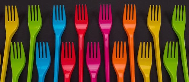 明るい背景に多くの色のプラスチック製のフォーク