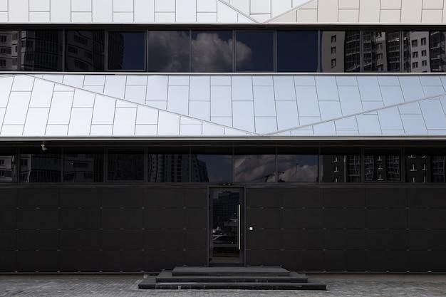黒く染められた窓とガラスのドアを備えたモダンでミニマルな黒と白の建物