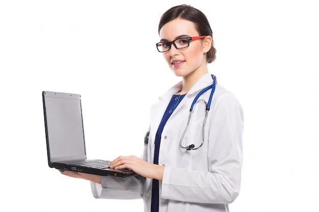 白い制服を着た彼女の手でラップトップを保持している聴診器で若い女性医師