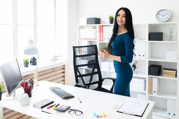 オフィスの若い女の子がテーブルのそばに立っていると彼女の手で赤いカップを保持しています。