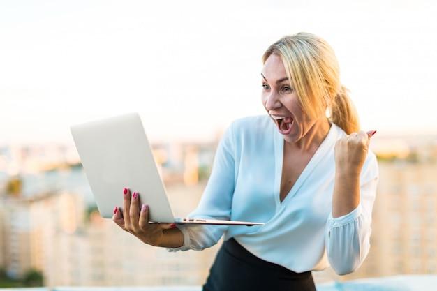 Красивая умная бизнес-леди стоит на крыше с ноутбуком в руках