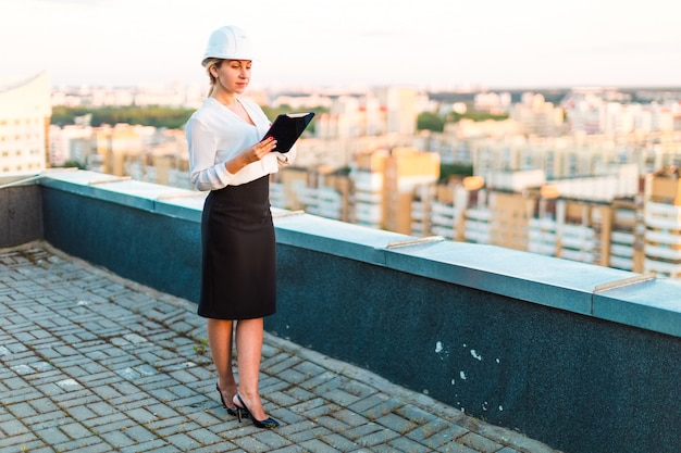 ヘルメットのかなり若い職長がタブレットを手に屋根の上に立つ、夕日を見て