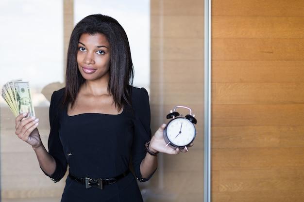 黒の強力なスイートでかなり、若いビジネス女性はお金と目覚まし時計の束を保持します