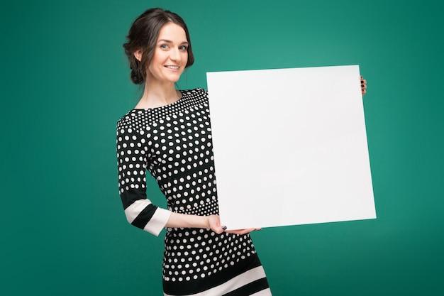 Образ красивой женщины в крапчатой одежде, стоя с бумагой в руках