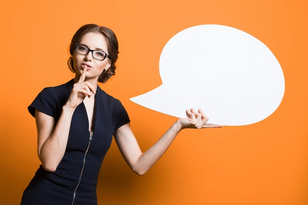 Портрет уверенно возбужденных красивая молодая деловая женщина с пузырем речи в руках
